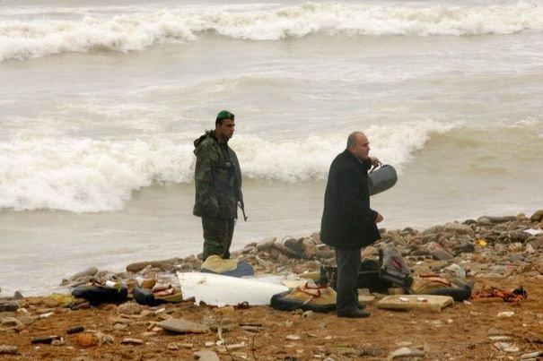Un homme inspecte les debris du crash de l'avion d'ethiopian airlines sur une plage de la cote libanaise le 25 janvier 2010